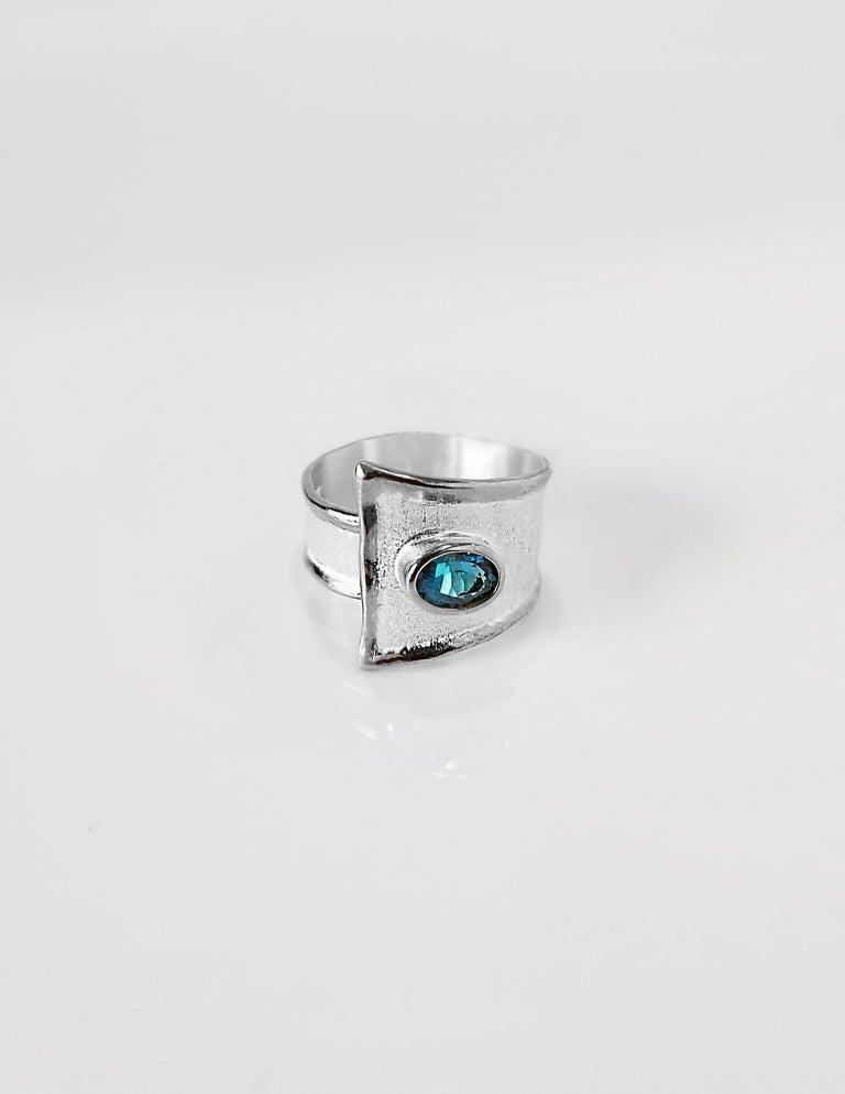 Yianni Creations Ammos Collection band Ring from Fine Silver featuring a 1.60 Carat London Blue Topaz complemented by unique techniques of craftsmanship - brushed texture and nature-inspired liquid edges. The core of this gorgeous