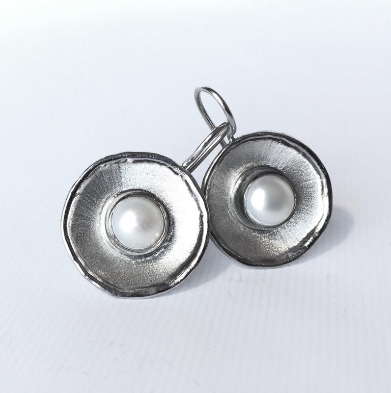 From Yianni Creations Ammos Collection, these are handmade artisan earrings from fine silver plated with palladium to resist against elements. Each earring feature 7mm round freshwater pearl. These round dangle earrings combine contrast of mat