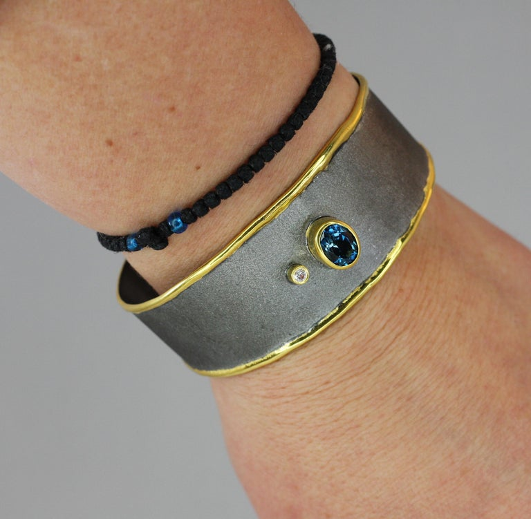 We are presenting Yianni Creations Handmade Artisan Bangle Bracelet from the new Eclyps Collection. Fine Silver 950 purity is here finished with Black Rhodium on the brushed background and with a thick overlay of 24 Karat Yellow Gold on the melted