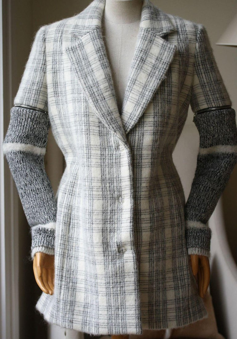 This plaid wool Yigal Azrouel coat features a notched collar, welt hip pockets and detachable exposed zipped marled knit sleeves. Hidden snap button front closure. 45% virgin wool, 44% mohair, 11% nylon. Fully lined.  Size - US 2 (UK 6, FR 34, IT