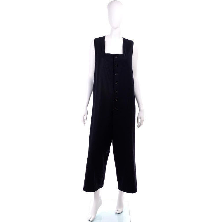 This is a wonderful Yohji Yamamoto vintage midnight blue jumpsuit from the 1990's.  This straight, sleeveless oversized jumpsuit is in a midnight blue gabardine wool twill with a square neckline. There are buttons down the center front and slash,