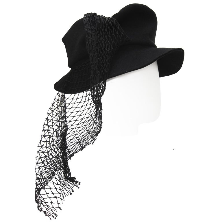 Rare Yohji Yamamoto black hat from circa SS 1999. The hat is in black thin wool with a flat top, asymmetric draped mesh net material. Truly amazing piece.  Inside hat measures : circa 59 cm