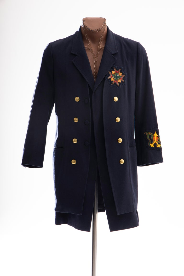 Yohji Yamamoto Pour Homme, Runway, Fall 2012 navy blue double-breasted coat with embroidered patches at chest, back and left sleeve cuff, two front pockets and two interior pockets, brass and fabric covered button closures at front and fully