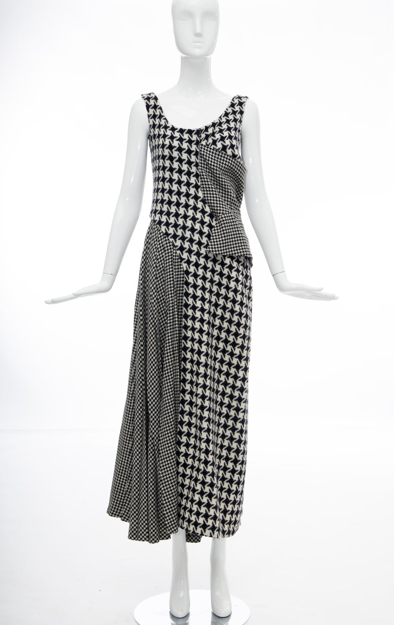 Yohji Yamamoto, Fall 2003 Runway wool sleeveless scoop neck dress featuring various sizes of houndstooth in both navy and black color ways, a side peplum and draped pleating at the right hip and back with concealed snap closures at back.   Designer