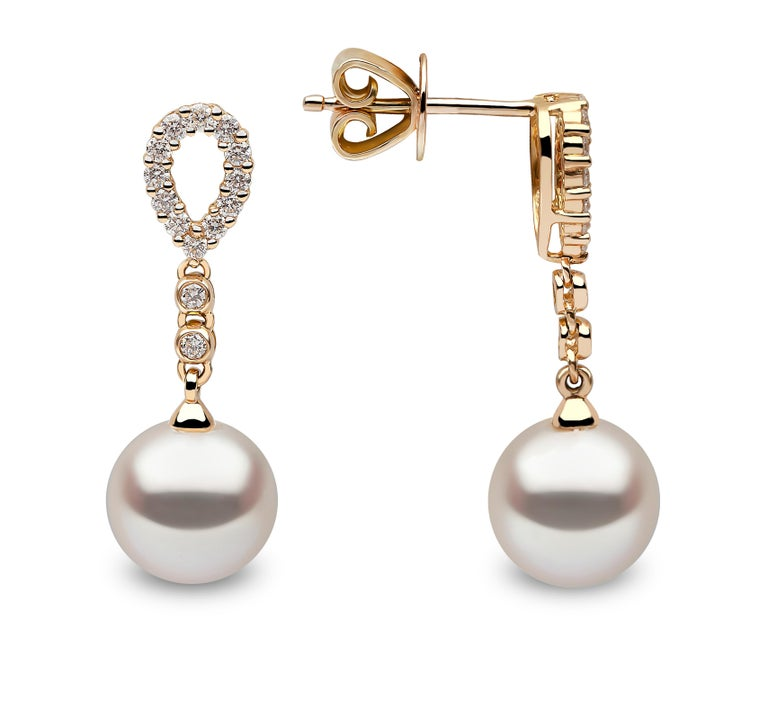 These delicate earrings by Yoko London features lustrous Freshwater pearls beneath an elegant arrangement of diamonds. The 18 Karat Yellow Gold setting perfectly enriches the white colour of the diamonds and the lustre of the pearls. These graceful