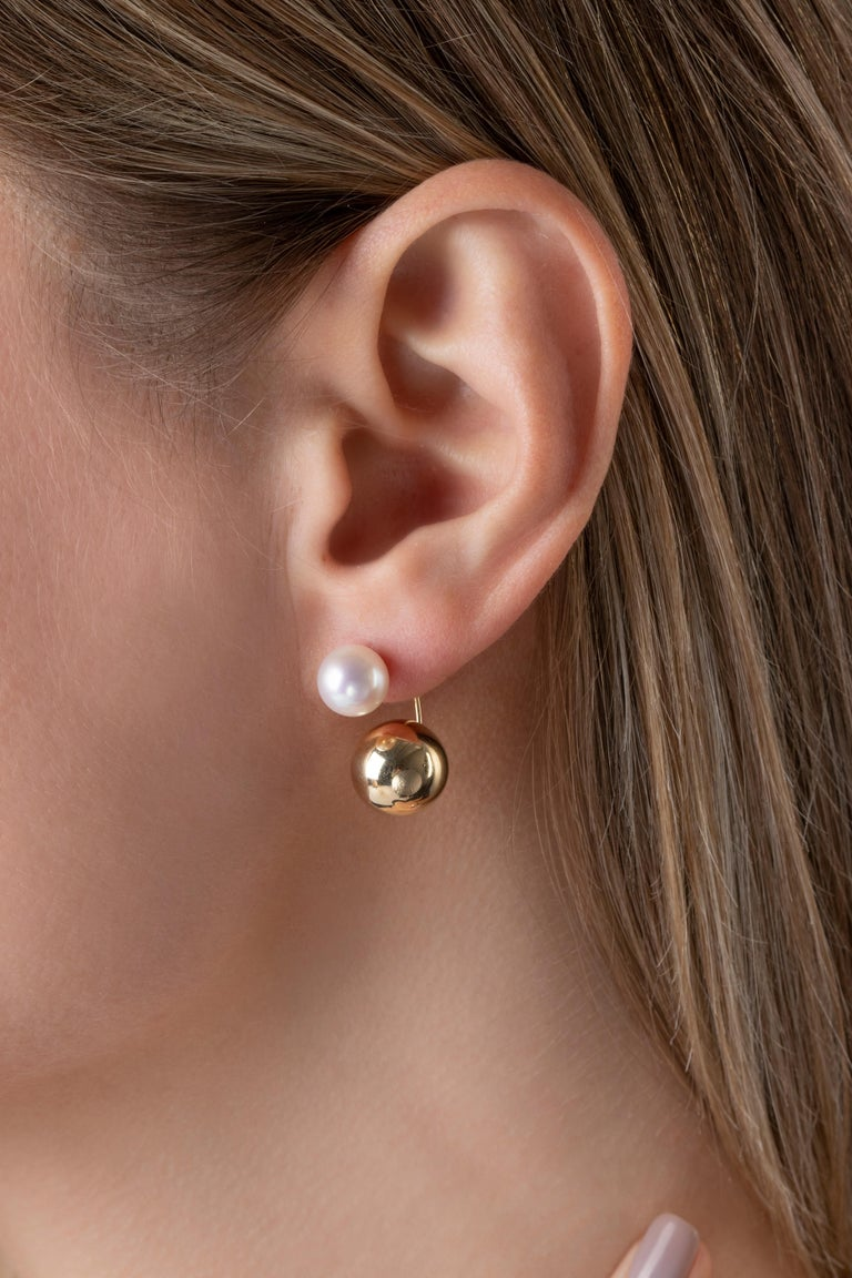 These striking earrings by Yoko London feature lustrous Akoya pearls atop a yellow gold sphere which sits beneath the lobe. Contemporary and elegant, these unique earrings will add a striking touch to any outfit.   -8-8.5mm Japanese Akoya Pearls