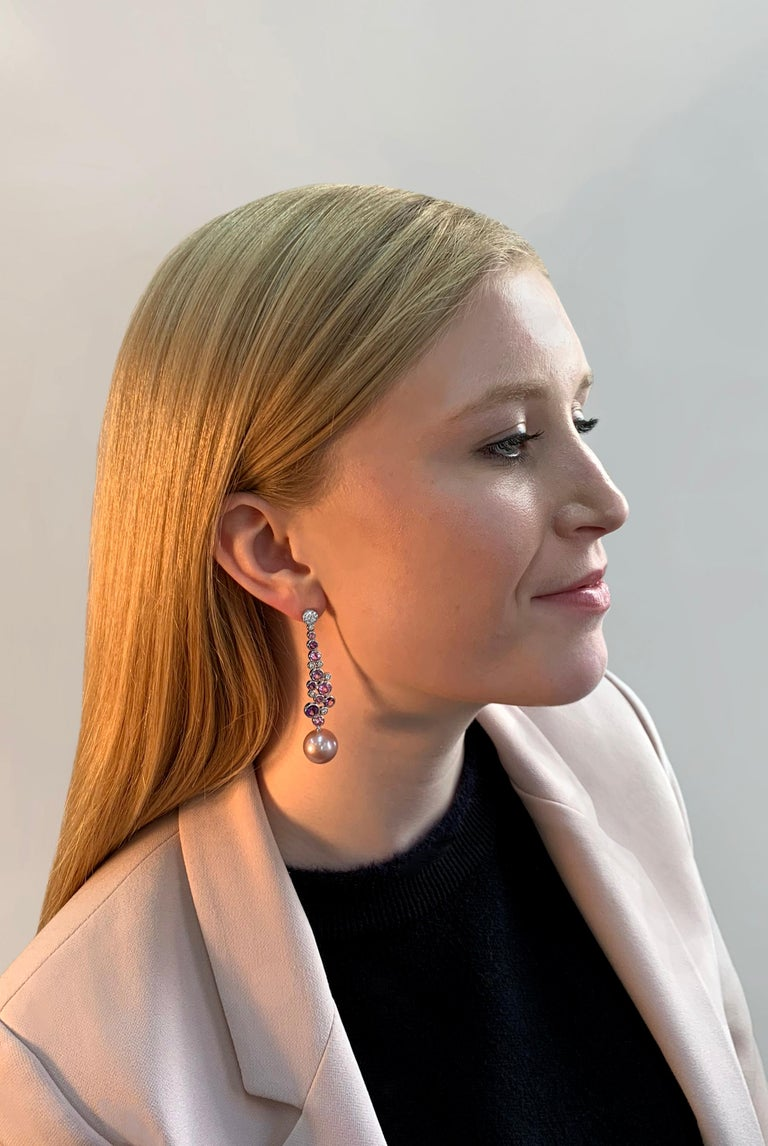 These unique earrings by Yoko London feature lustrous Freshwater pearls beneath cascading diamonds, amethysts and pink sapphires. Set in 18 Karat White Gold to enrich to vivacity of the colours, these lovely drop earrings will add a playful pop of