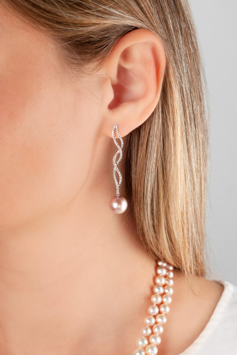 These elegant earrings by Yoko London feature vibrant, natural colour pink Freshwater pearls beneath delicate diamond twists. Set in 18 Karat white gold to perfectly enrich the colour of the pearls and the sparkle of the diamonds, these intricate