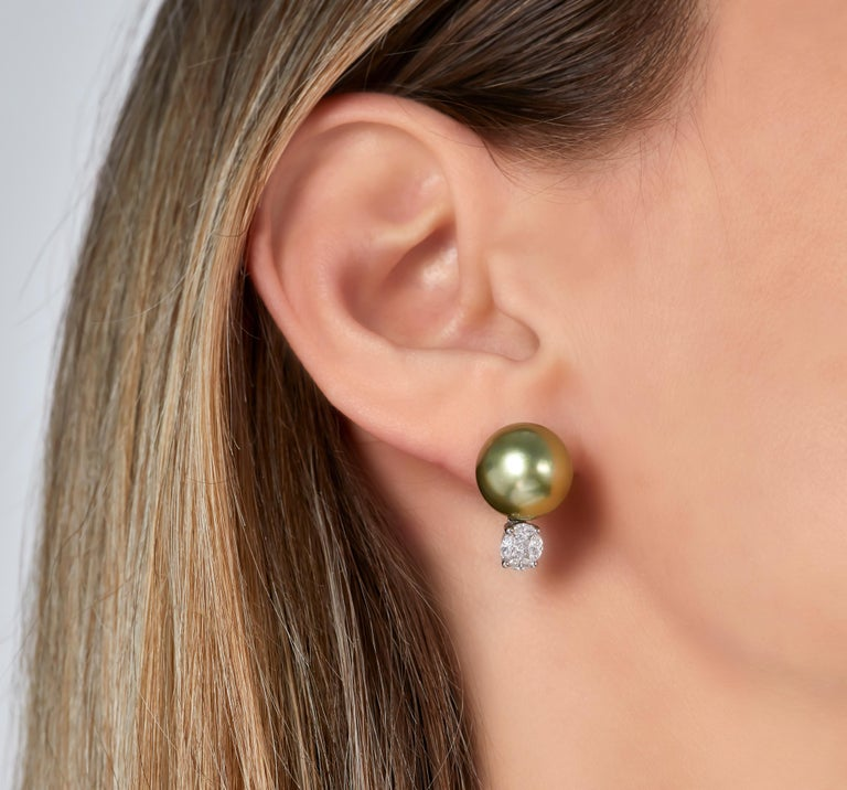 These alluring earrings by Yoko London feature 13-14mm Pistachio-Colour Tahitian Pearls sat atop a scintillating arrangement of diamonds. To achieve their eye-catching and unique colour, the Tahitian pearls featured in these earrings have been