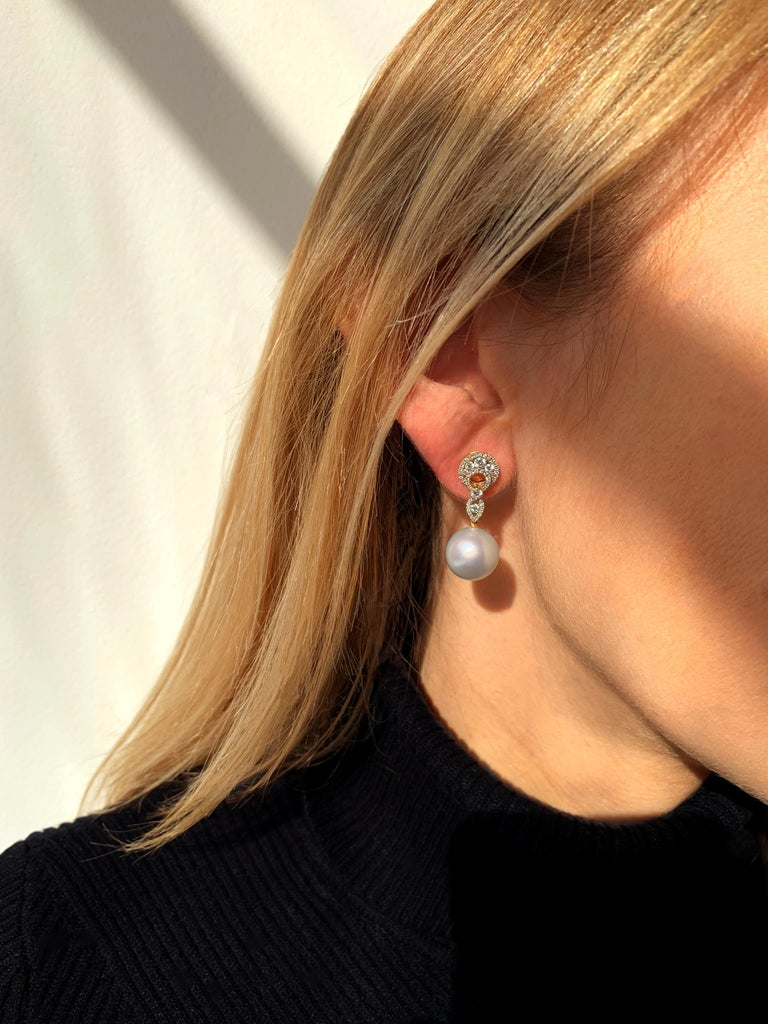 These scintillating earrings by Yoko London feature lustrous South Sea pearls beneath an elegant arrangement of diamonds. The 18 Karat yellow gold setting serves to enrich the radiance of the diamonds and the crisp white lustre of the South Sea