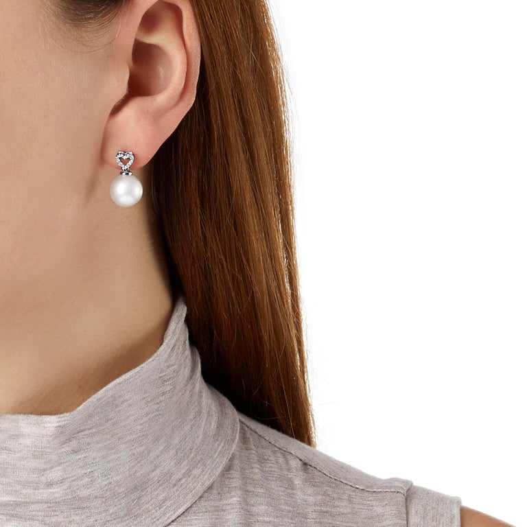 These lovely earrings by Yoko London feature lustrous South Sea pearls beneath a playful diamond heart motif. Contemporary and elegant, these earrings will add a touch of sophistication whenever they are worn. The perfect gift for a loved one, these