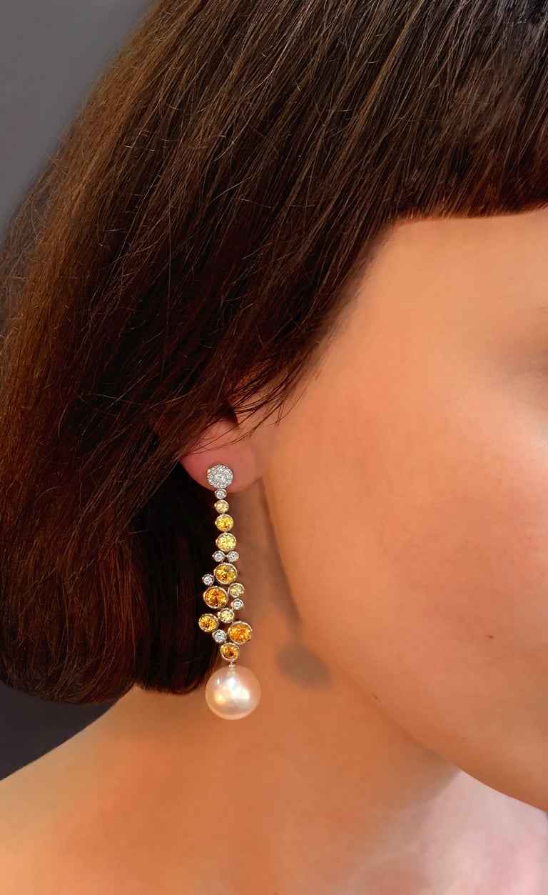 These unique earrings by Yoko London feature lustrous Freshwater pearls beneath cascading diamonds and orange sapphires. Set in 18 Karat White Gold to enrich to vibrancy of the orange hues, these lovely drop earrings will add a playful pop of colour