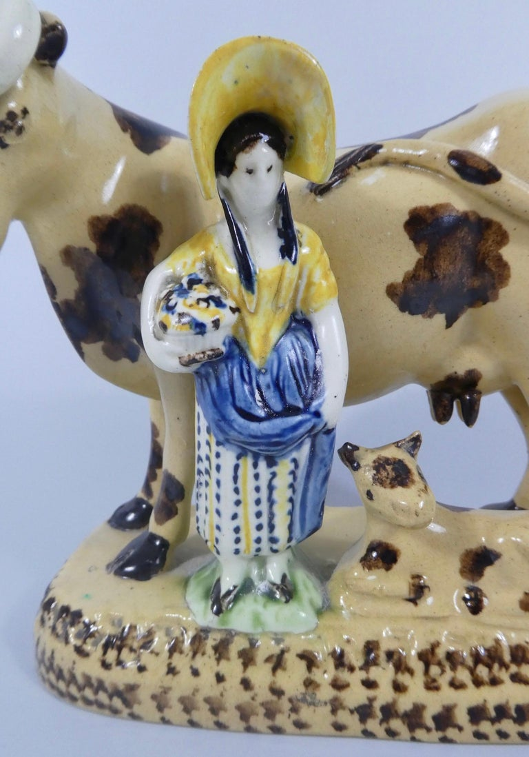 Yorkshire pottery Prattware group, circa 1820. Modelled as a shepherdess, holding a basket,and stood with a cow and its calf. The shepherdess, decorated in Pratt coloured glazes, whilst the cow and the calf, are decorated with brown spits, on a buff
