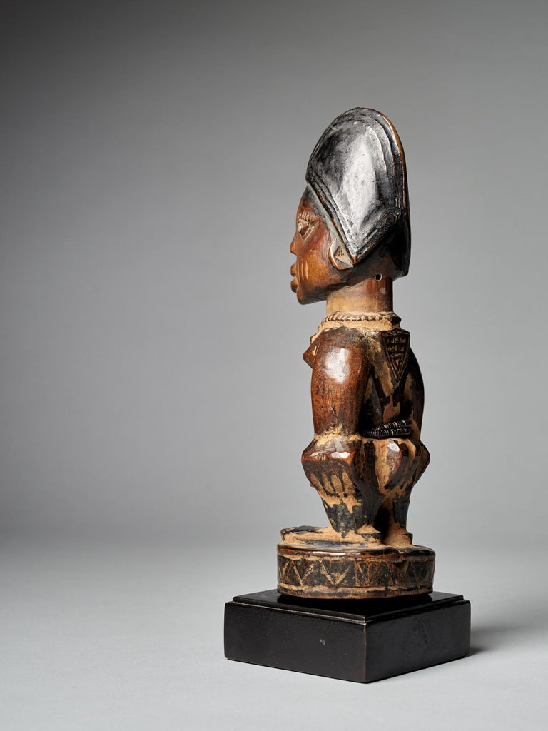 A finely carved big Yoruba Male Ibeji figure with tall headdress, expressive eyes, original bead belt and heavy wear and polish from native use. Areas of encrusted cam wood powder between arms and around feet. Though the cause of the high rate of