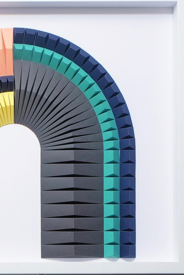 This beautiful geometric abstract wall sculpture is made out of colored laser cut paper that was hand folded by Yossi Ben Abu. It comes in white wooden frame and a non glare museum glass.