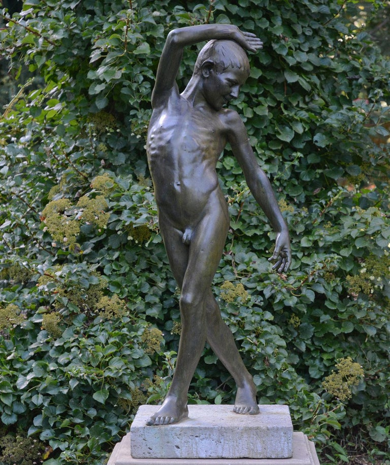 An exceptional bronze figure of a youth portrayed as nude and standing in a fluid pose, the face with jubilant expression and downward gaze, with one arm upswept and the other down, with one leg crossed in front of the other, suggesting movement,