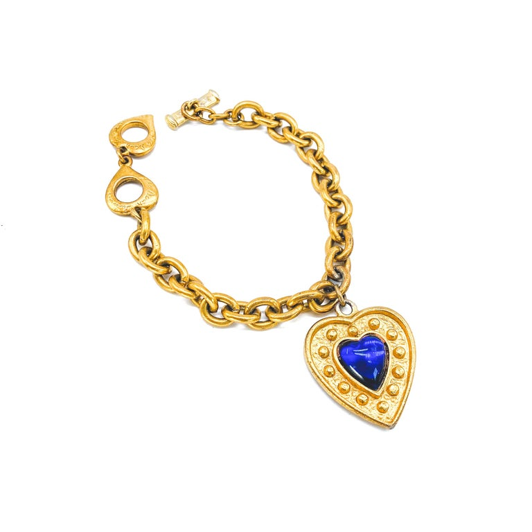 Yves Saint Laurent Vintage 1980s Bracelet  Detail -Made in France in the late 1980s -Expertly crafted from gold plated metal -Chunky gold chain -Large YSL heart shaped charm set with a lapis lazuli coloured stone  Size & Fit -Length approx 7 inches