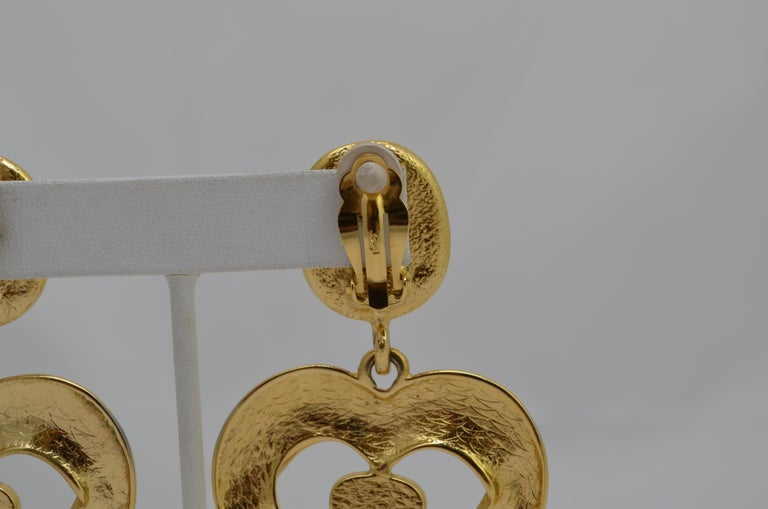 YSL Gold Clip-On Earrings with Heart Motif -- earrings are featured in a gold-tone metal with red/pink stones with clip-on fastenings. Signed YSL at the backs of each earring.  Length - 3'' Drop Length - 2''