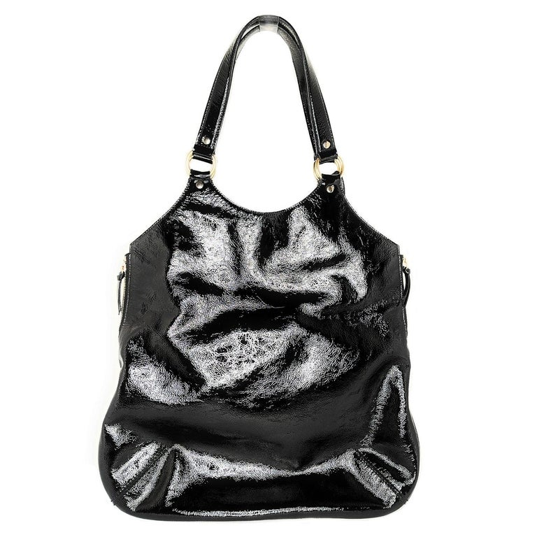 This stylish tote is crafted of fine black patent leather. The bag features leather strap top handles with polished brass hardware. The top opens with magnetic snap and side zippers to a satin interior with zipper and patch pockets.  Designer: YSL
