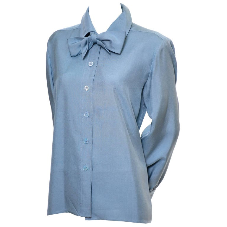 This lovely vintage blue silk long sleeve blouse was designed by Yves Saint Laurent in the late 1970's. This raw silk button front blouse has a fabric tie at the neck that can be tied into a knot or a bow.  The blouse is labeled a French size 38 and