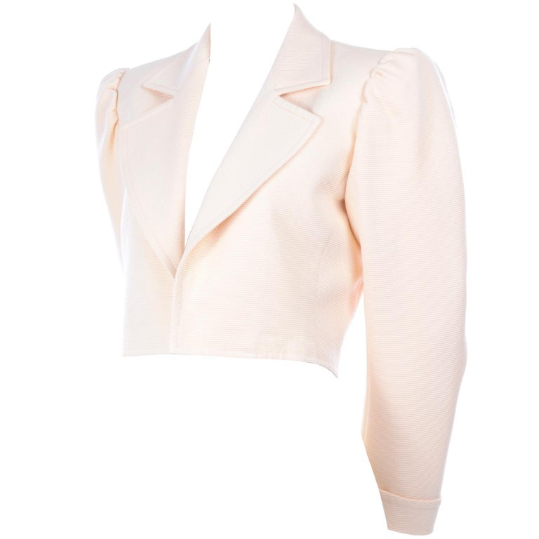 This is a versatile Yves Saint Laurent vintage cropped jacket with and open front. It made in a ribbed cream fabric with a cream silk lining. This is a great YSL blazer that can be worn today effortlessly with its gathered shoulders and cuffed
