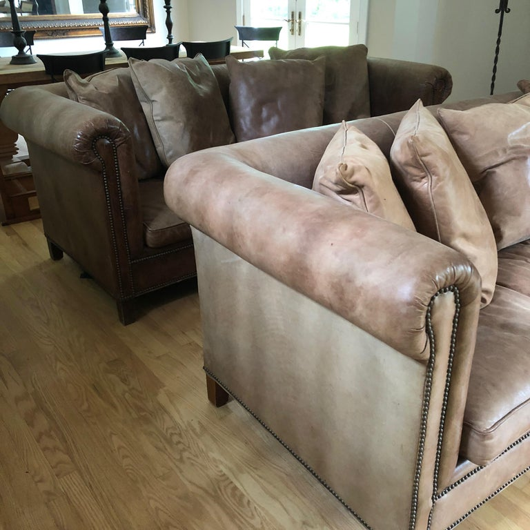Two fabulous slightly distressed supple soft leather Ralph Lauren sofas having down seat cushions and 4 pillows each. As is customary with leather, one is a slightly different shade of brownish taupe than the other. Note: Will split the pair. A