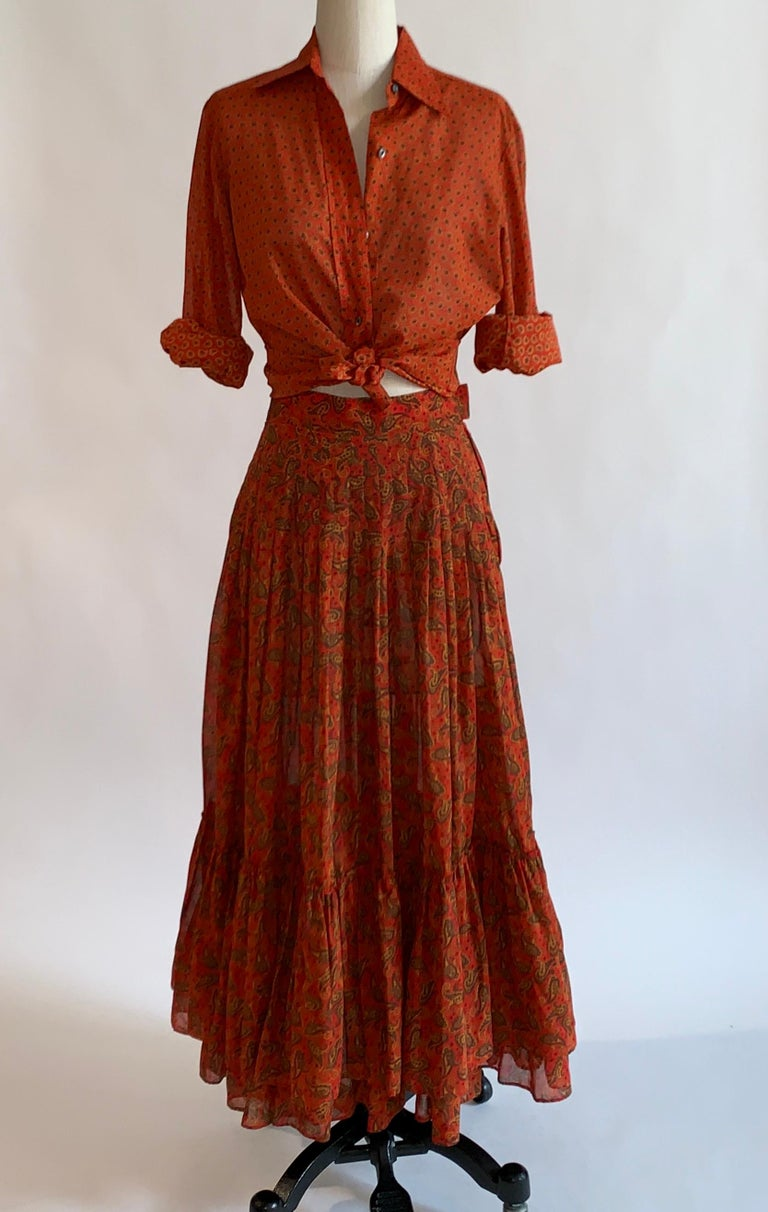 Vintage 1970s Yves Saint Laurent Rive Gauche red orange paisley print prairie style skirt with tiered ruffle hem and coordinating (but not matching) button up blouse. Collared blouse buttons at front. Skirt fastens with side zip and two hooks.