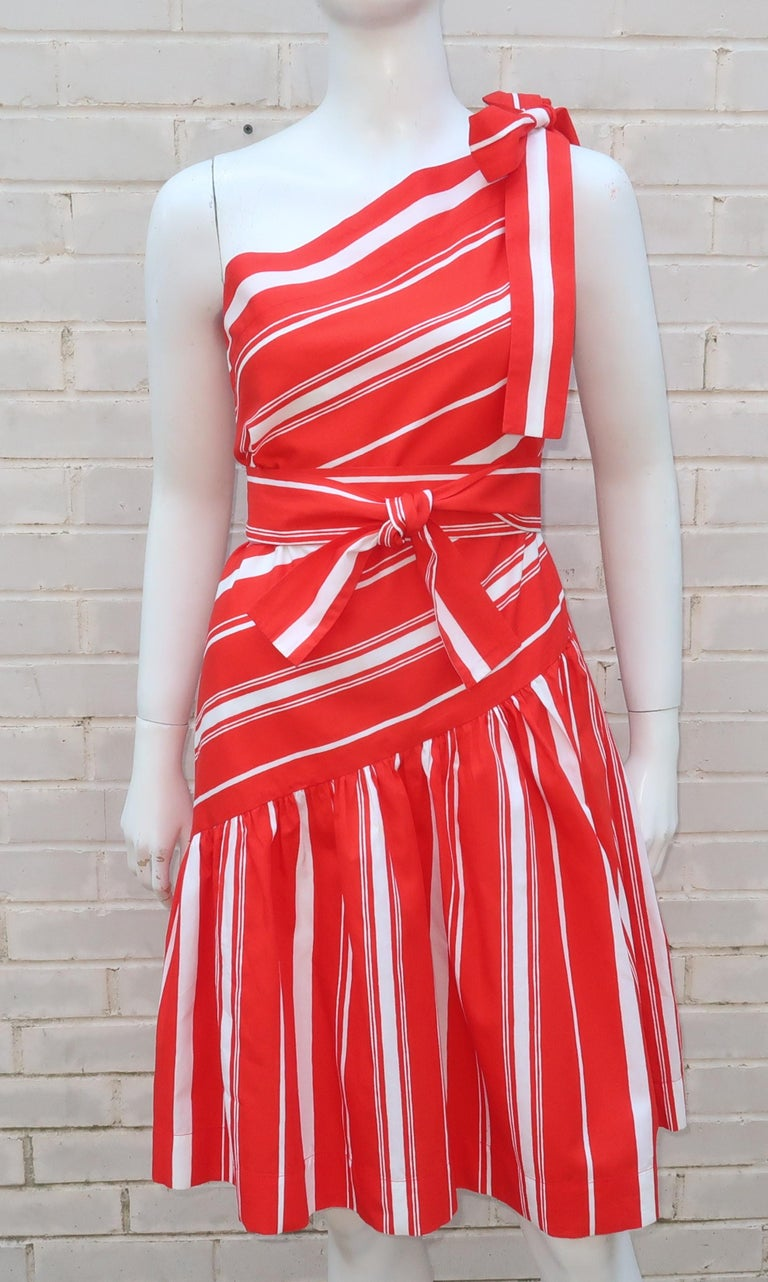 This adorable Yves Saint Laurent red and white candy stripe sundress is a yummy confection.  The crisp cotton fabric features an asymmetrical one shoulder drop waist bodice with a gathered skirt all accented by a tie at the shoulder and another for