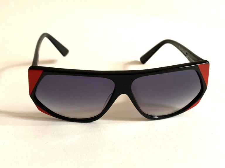 Vintage 1980s Yves Saint Laurent geometric sunglasses in black plastic with red detail at corners and sides. Grey lenses. Gold YSL logo at right temple. From the Museum at FIT.  Frame measures approximately 5 3/8