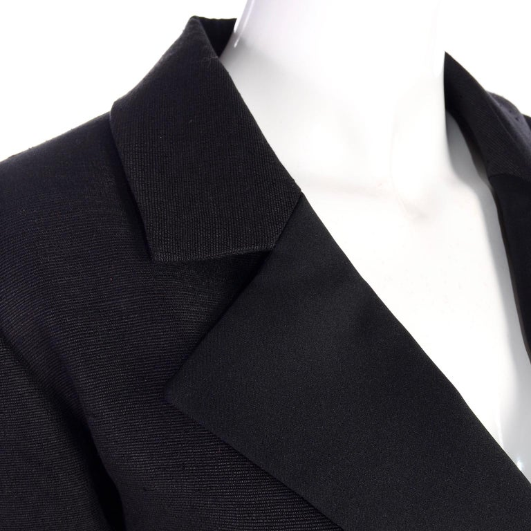 Yves Saint Laurent Rive Gauche black skirt suit that looks like raw silk. The blazer jacket is double breasted with textured large black buttons. The skirt has nice pleats in front, with a front pleated over slit. The lower lapel on the jacket is a