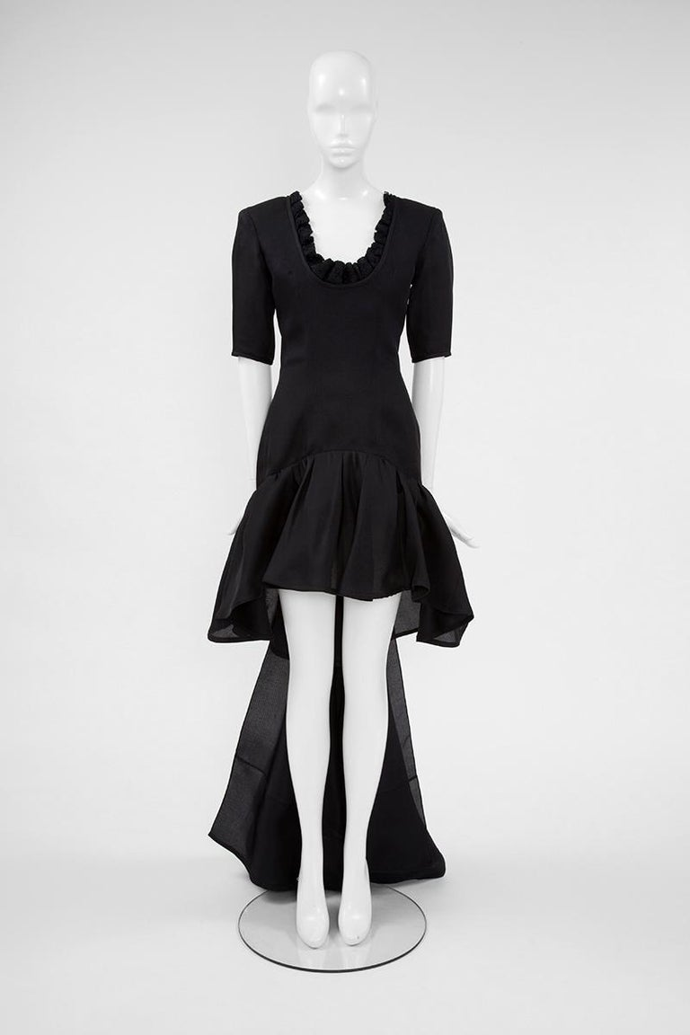 Celebrate the magic of getting dressed-up for a special occasion with this standout late 80's - early 90's evening piece by YSL ! Cut from black silk gazar to hug the curves, this dress features short sleeves, an asymmetric skirt and a bow train.
