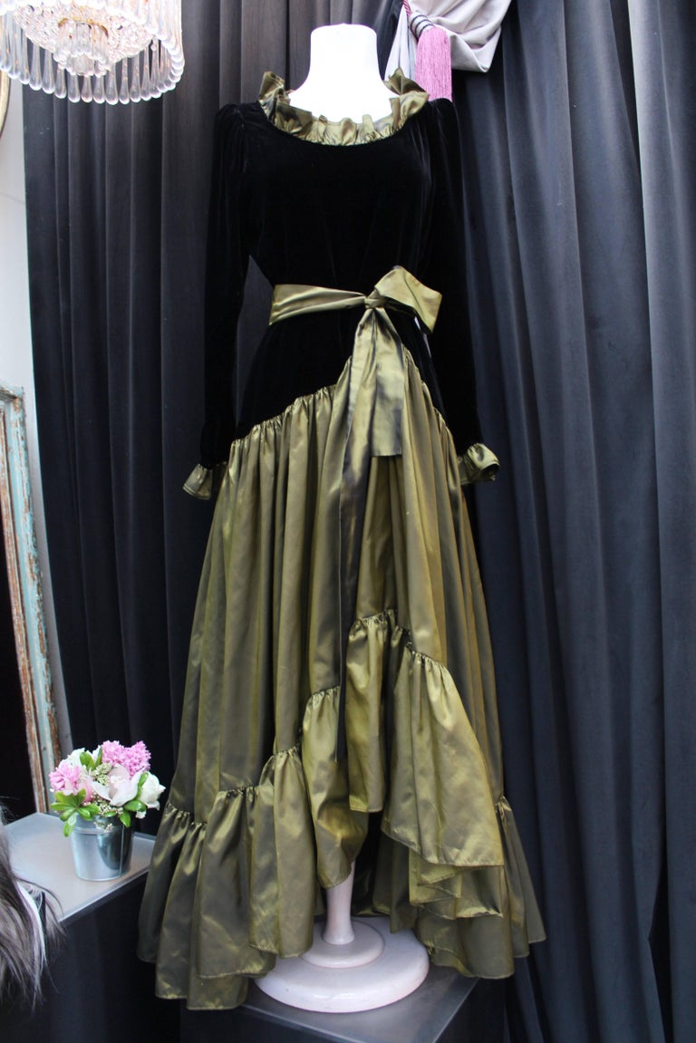 YVES SAINT LAURENT (Made in France) – Long sleeve long evening dress with asymmetrical cut. The top is made of black silk velvet. The cuffs and collar are trimmed with flounced iridescent bronze green taffeta. The asymmetrical bottom is composed of