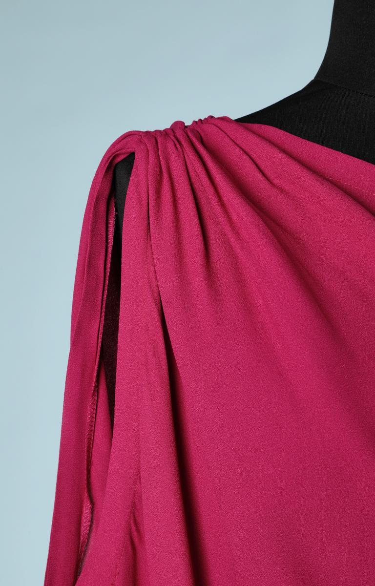Sleeveless evening long dress in asymmetrical fuchsia pink crepe, with a bare shoulder pad and draped over the hips, designed by Yves Saint Laurent Rive Gauche. Size 38 French