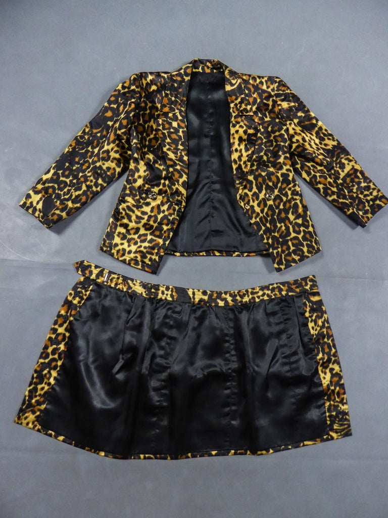 Circa 1990 France  Yves Saint Laurent Skirt suit without label from the1990s. Set in printedpanther silk satin. Crossed jacket with topstichting, large lapels and pockets. Translucent buttons with golden panther effect. Short wrap skirt with side