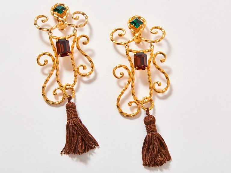 Yves Saint Laurent, gold tone, baroque motif,  jumbo size, clip on earrings, having topaz and emerald, colored cut stones detail, and brown tassels that sweep the shoulders.