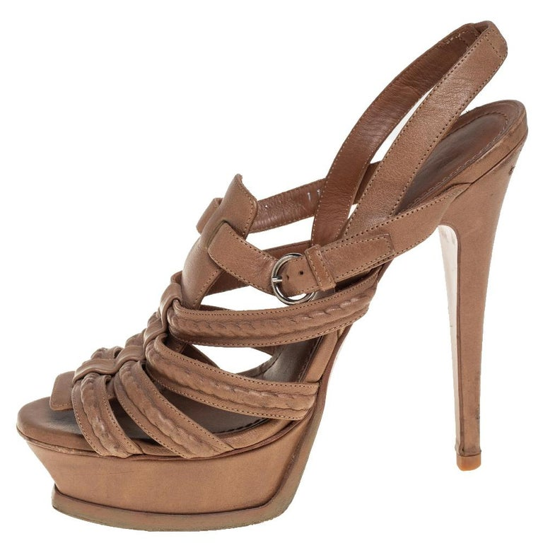 These Yves Saint Laurent sandals are the epitome of elegance and poise. They are made from beige leather and designed with braided straps, high heels supported by platforms, and slingbacks.