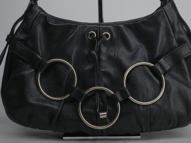 Shoulder Bag with gold circular link hardware and tassel detail. Zipper Top and adjustable strap