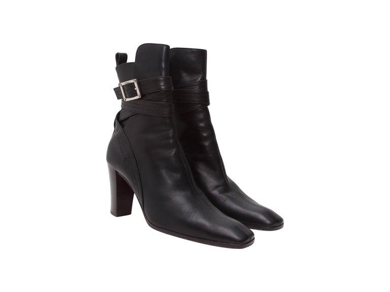 Product details:  Black leather ankle boots by Yves Saint Laurent.  Wrap-around shaft strap with adjustable buckle closure.  Rounded square toe.  Silvertone hardware.  3.5