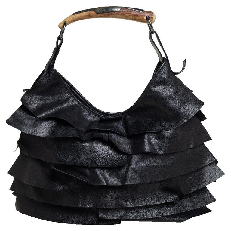 This hobo by Yves Saint Laurent has been perfectly designed to accompany you to all your fashionable outings. It is made from black leather and has gorgeous ruffles and the brand label flaunted on the front. The suede insides are spacious and the