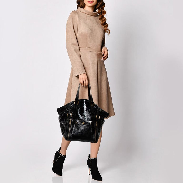 Every closet deserves a bag that is as luxe and functional as this Downtown tote from Yves Saint Laurent. Crafted using patent leather, the bag has been styled with gold-tone zippers and buckles. It features two handles and a top zipper that leads