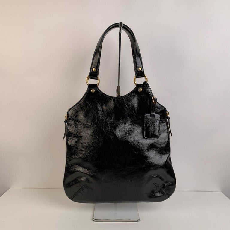 Yves Saint Laurent Black 'Metropolis Tribute Bag', crafted in black shiny leather. It features a sleek design in with side zip detailing , an ID tag and gold metal hardware. Magnetic button closure on top. Black satin lining. 1 side zip pocket