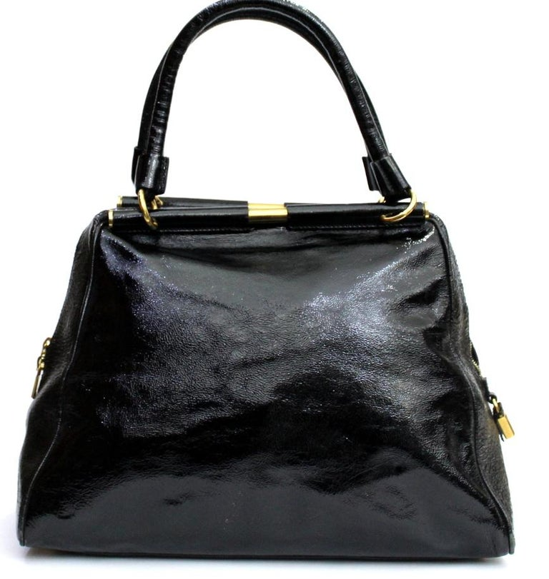 Yves Saint Laurent bag made of black gloss patent leather, with golden hardware. Double handle, zip closure.Internally large. Suitable for both day and evening.The bag is in good condition, with some signs of wear on the lower corners.