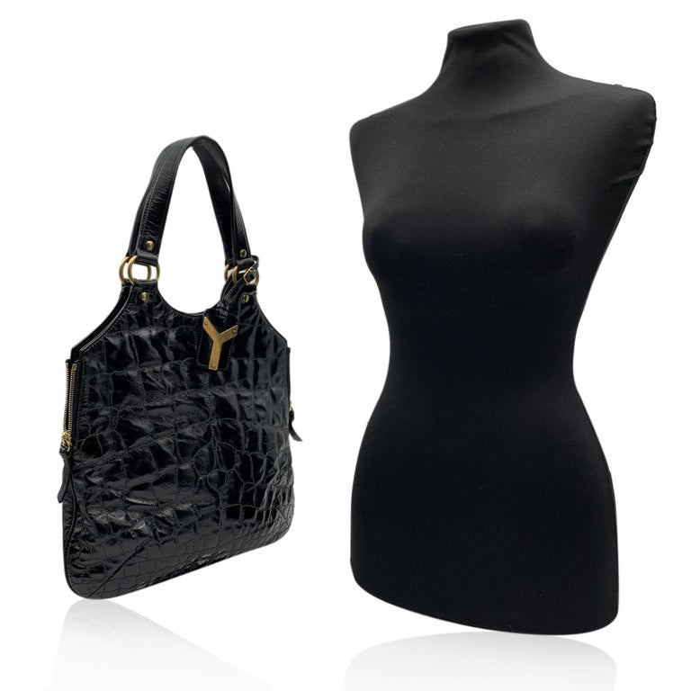 Yves Saint Laurent Black 'Metropolis Tribute Bag', crafted in black shiny leather with a quilted embossed croc-look. It features a sleek design in with side zip detailing , an ID tag and gold metal hardware. Magnetic button closure on top. Black
