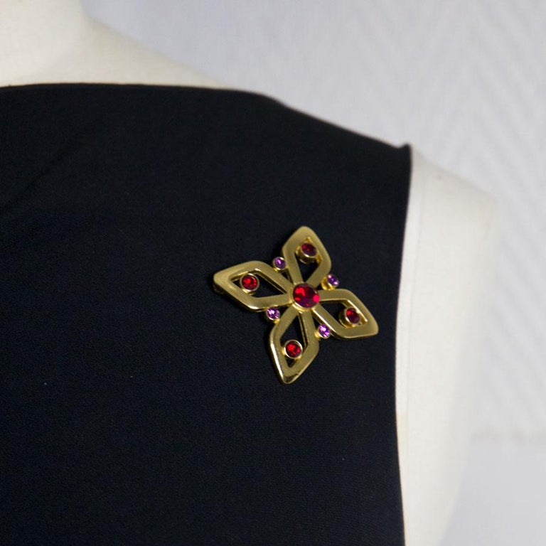 YSL Yves Saint Laurent brooch in gold metal, set with fancy garnet and purple stones. In very good condition. Made in France. Dimensions: 5.5 x 4 cm Delivered in a non original pouch