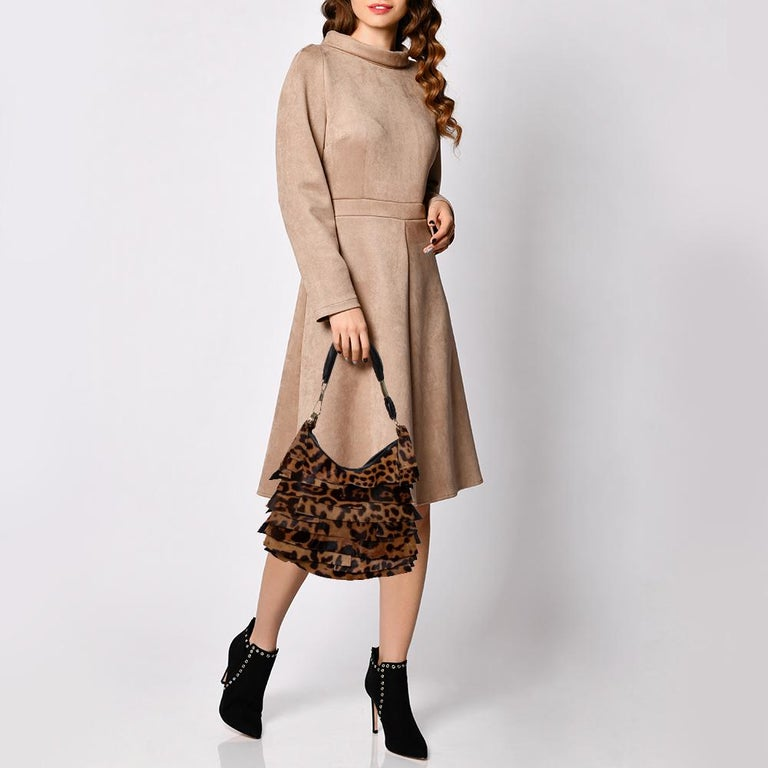 This hobo by Yves Saint Laurent has been perfectly designed to accompany you to all your fashionable outings. It is made from leopard-printed calf hair and leather and has gorgeous ruffles and the brand label flaunted on the front. The suede insides