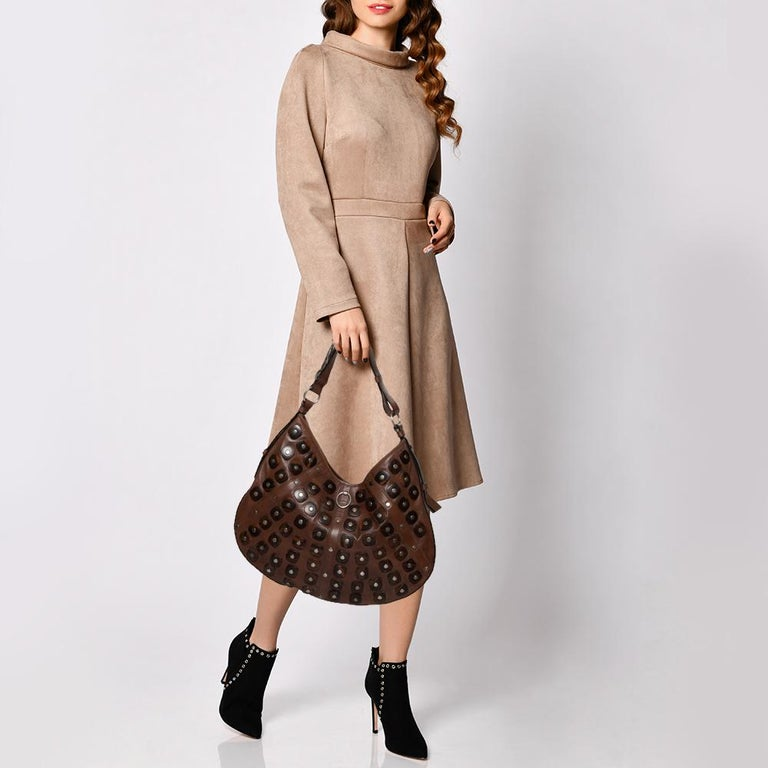 Stylish and functional, this bag by Yves Saint Laurent is great for elevating your daily ensembles. It has been crafted from quality leather in Italy and comes in a lovely shade of brown. It has a single handle, a shoulder strap, stud detailing on