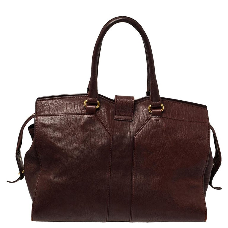 This elegant burgundy Cabas Chyc tote from Saint Laurent is ideal for everyday use. Crafted from leather, the bag is detailed with a gold-tone Y motif snap closure and dual-rolled handles. The top zip closure opens to a spacious interior that is