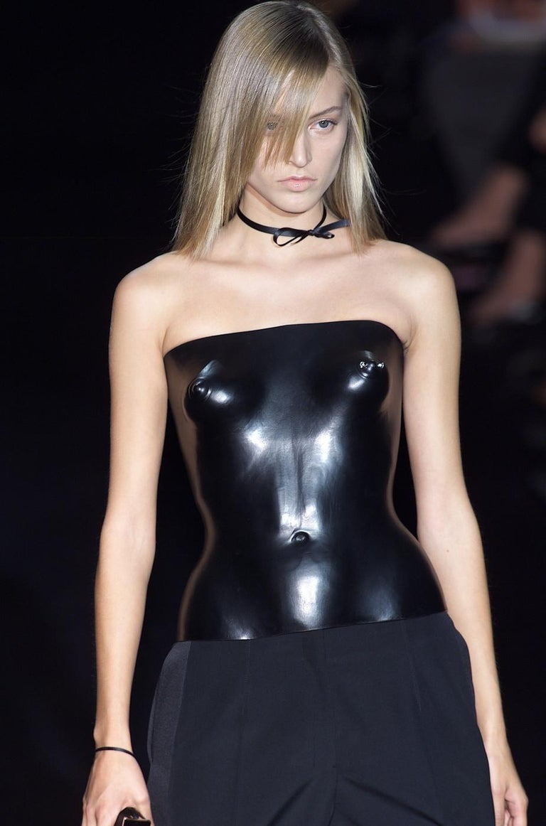 Runway ensemble from Tom Ford's first collection at Yves Saint Laurent, comprising: black leather corset, in which the naked torso of a woman is sculpted from the chest to the hip, decorated with a piercing on the left nipple with a square silver