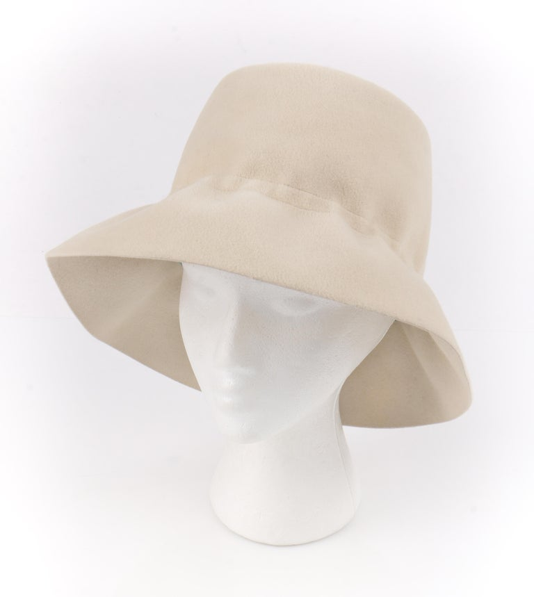 YVES SAINT LAURENT c.1960's YSL Cream Felted Fur Structured Bucket Hat   Circa: 1960's Label(s): Yves Saint Laurent / Paris - New York / Luxuria Imported Body Made In Italy Style: Bucket Hat Color(s): Cream and brown Lined: No  Unmarked Fabric
