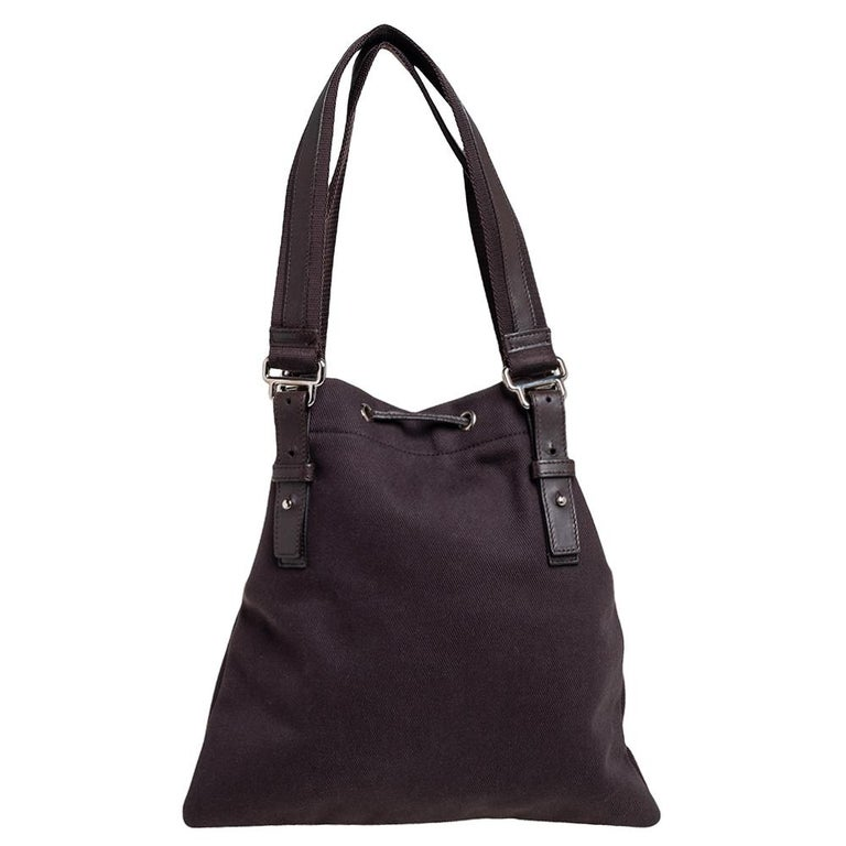 This Kahala tote from Yves Saint Laurent is crafted from canvas and velvet, and detailed with the signature YSL on the front. It comes with two handles, a drawstring closure, and a satin-lined interior that can hold all your daily necessities.